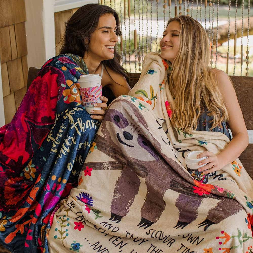 Two girls cuddling up to cozy blankets on porch