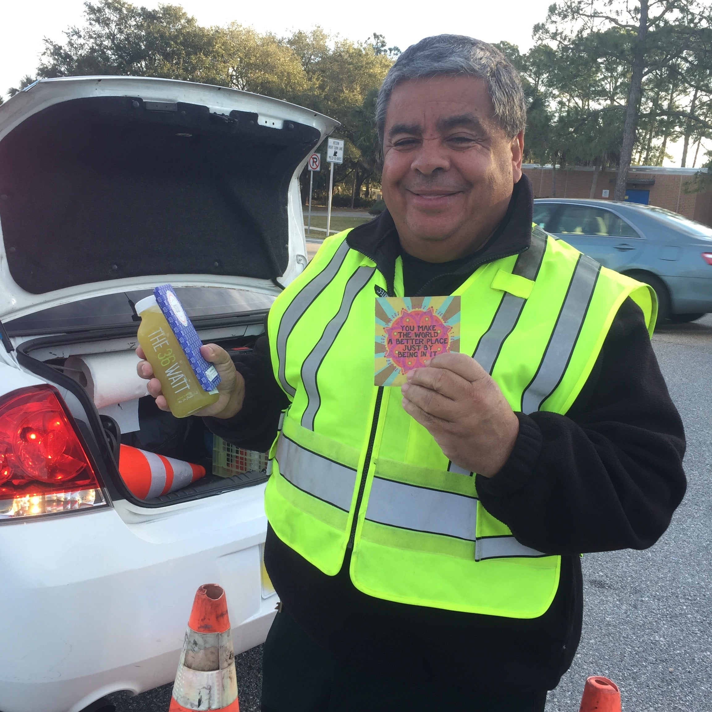 Our local traffic officer holding an organic juice and a chocolate bar