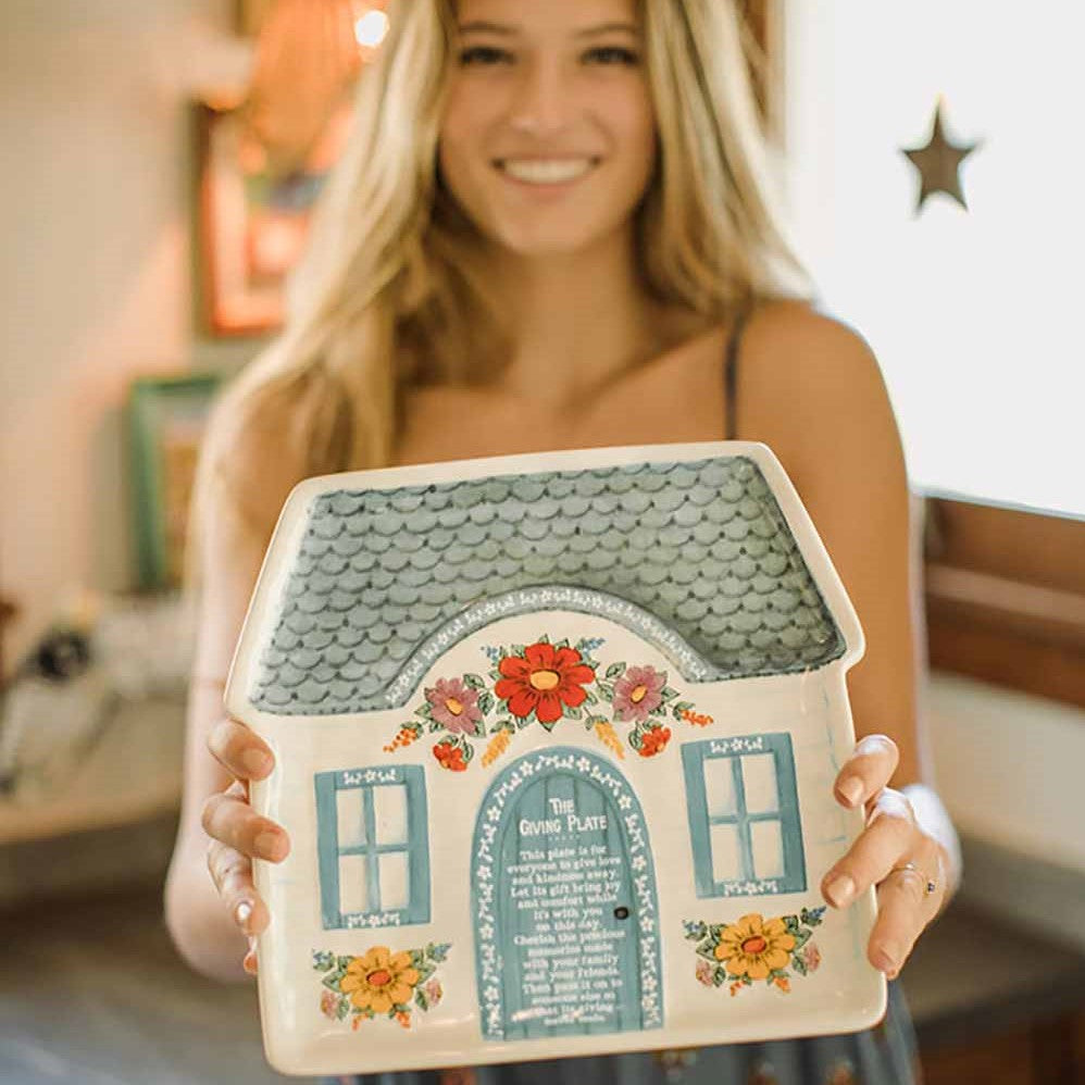 girl holding cottage giving plate