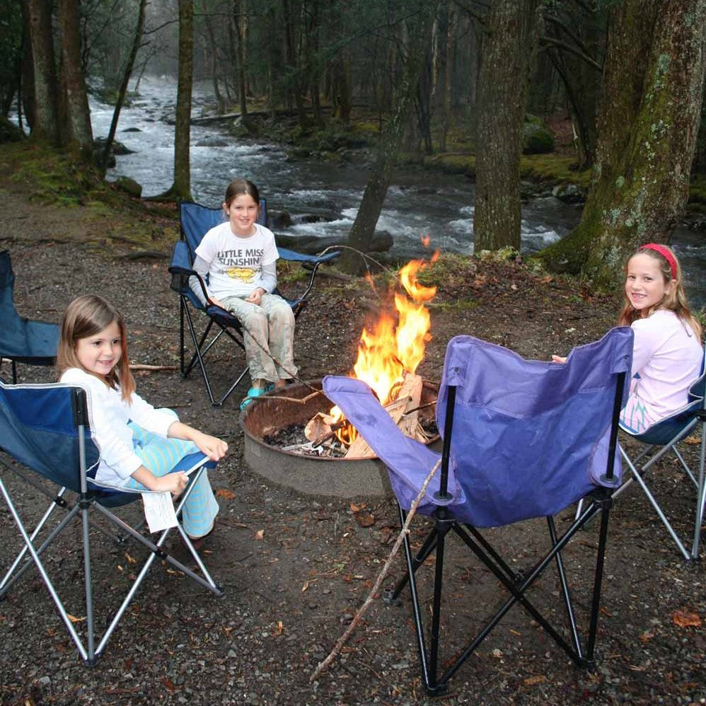 girls hanging around campfire