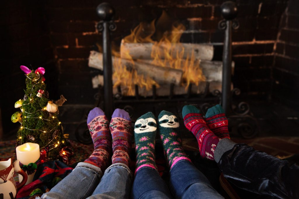 Cozy socks by a fire to help reduce holiday stress