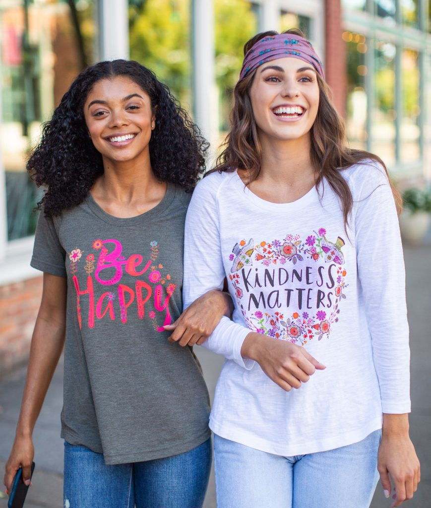 Girls wearing tees that say be happy and kindness matters