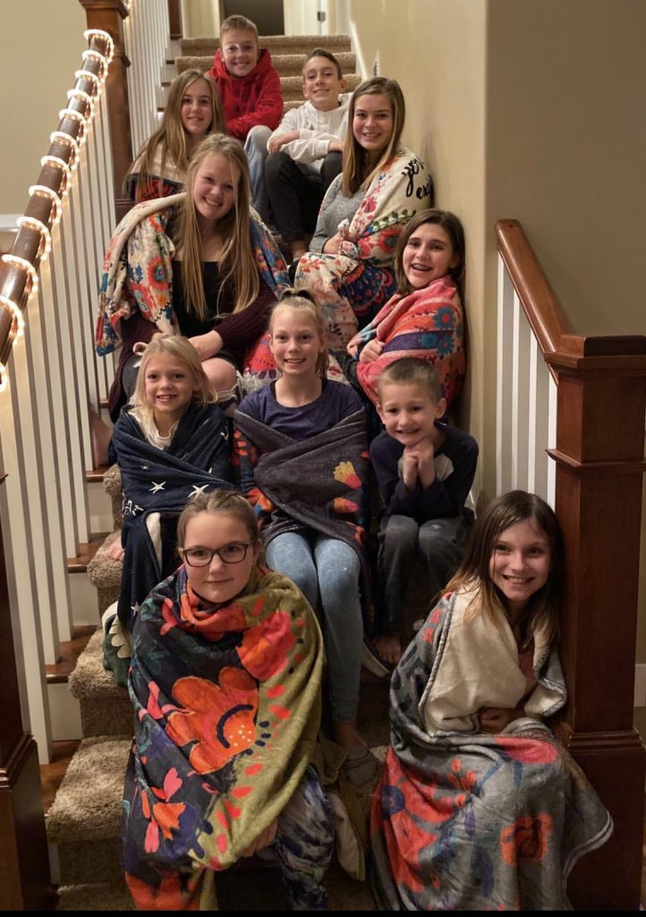Girls wrapped in cozy tapestry blankets