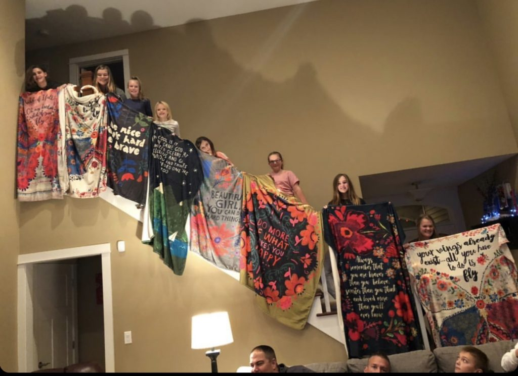 Girls displaying tapestry blankets on staircase
