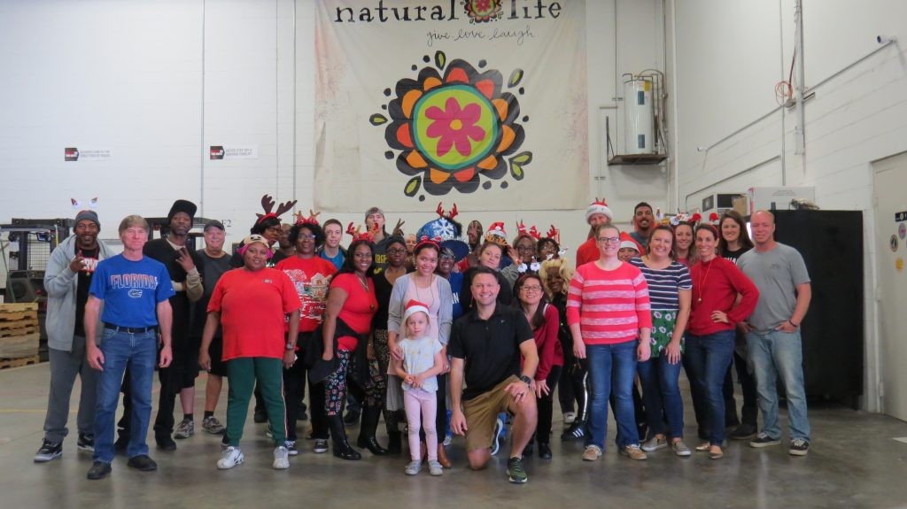 Warehouse team posing in front of Natural Life banner