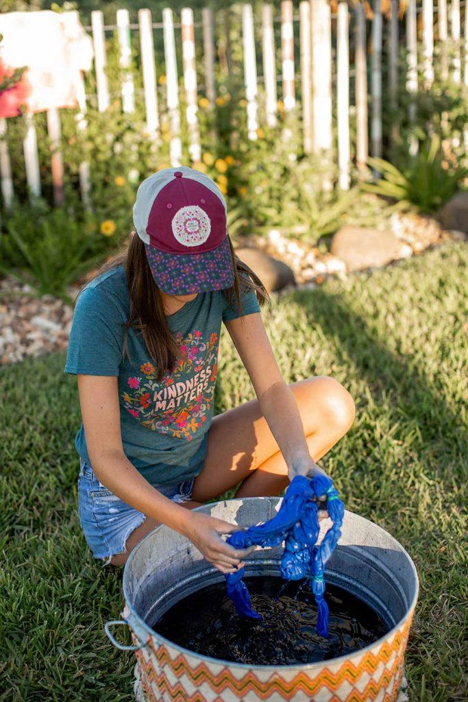 girl wearing cute tee and hat and doing DIY tie-dye