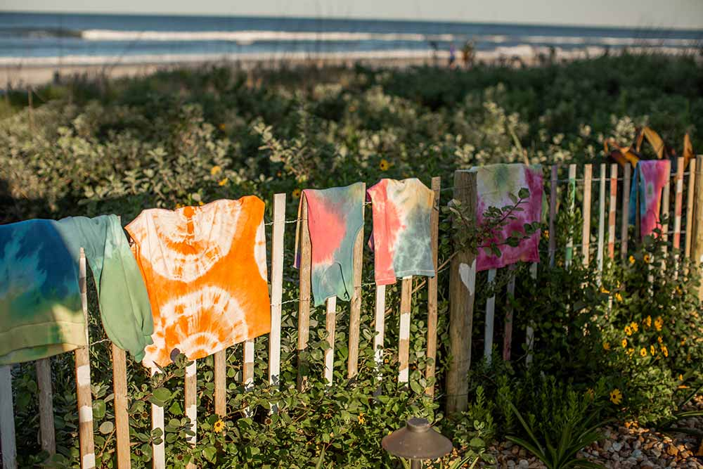 DIY tie-dye clothes hanging on a fence!