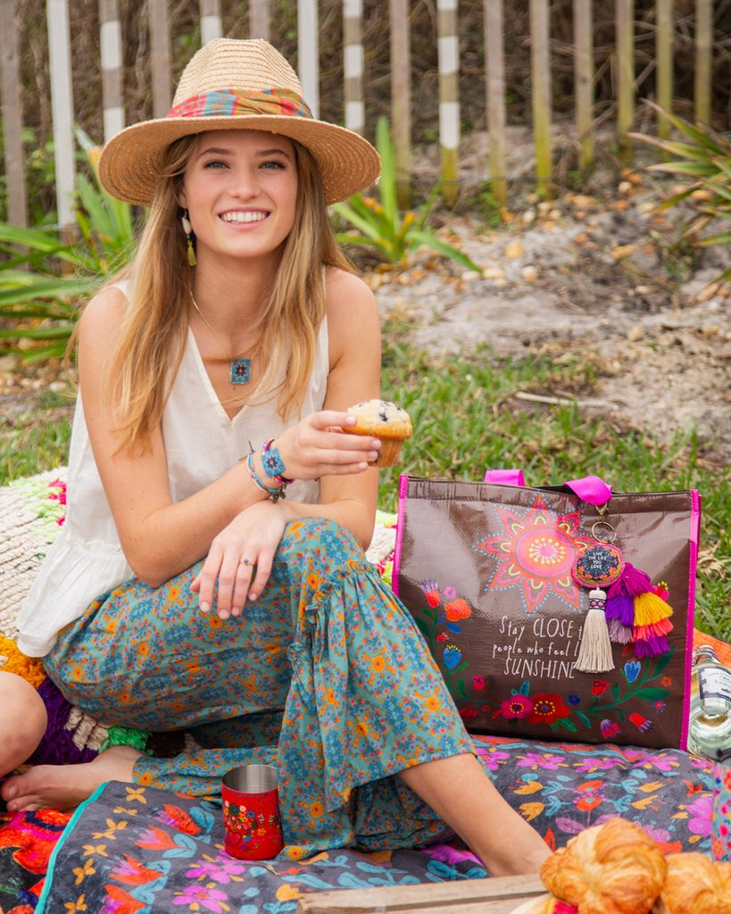 Girl on a picnic blanket holding a cupcake.