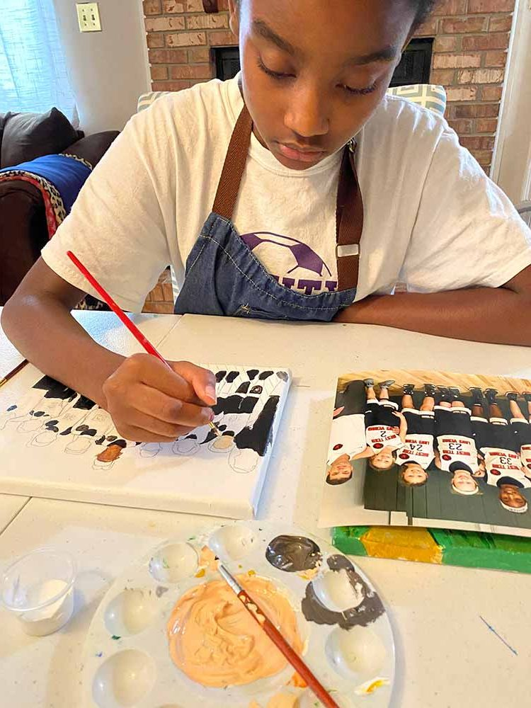Ava Ingle painting one of her art pieces sold for her community for donations for Keep my Hood Good