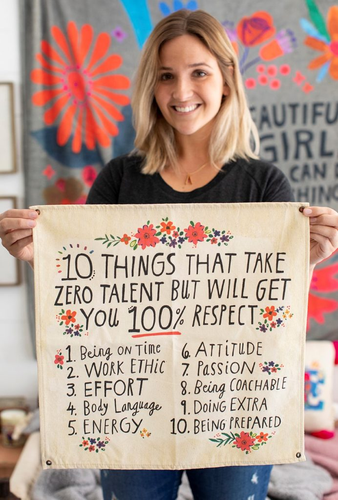 Girl holding mini canvas tapestry that lists 10 things that will get you respect. We love teachers and this makes the perfect gift for them for their classroom!