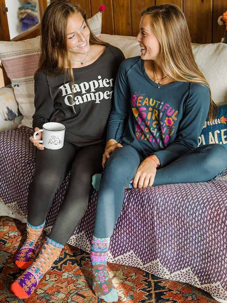Two girls drinking coffee on couch