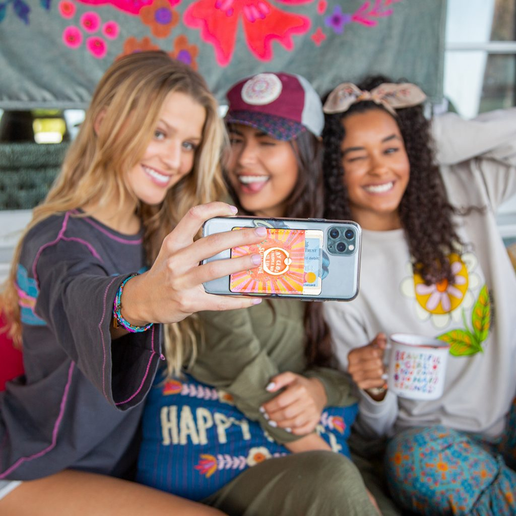 Three girls taking selfie with Natural Life phone pocket on the back of the phone.