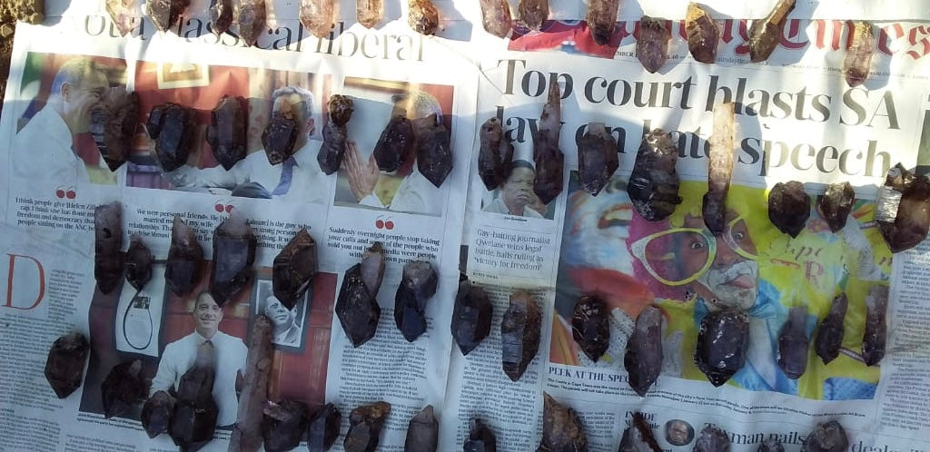 A flat of natural Shangaan Amethysts spread out over a local Zimbabwe newspaper.
