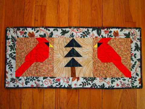 Cardinals & Pines Table Runner with Light Falling Leaves Background