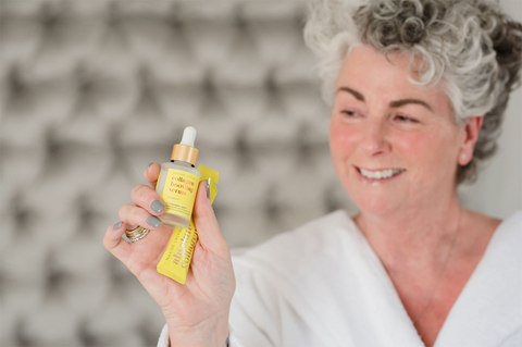Maxine Laceby holding a yellow Absolute Collagen serum bottle and sachet and smiling against a grey background