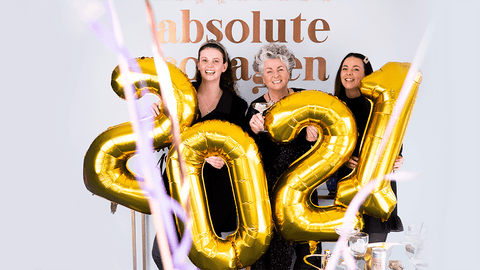 Photo showing Maxine, Margot and Darcy Laceby smiling in front of an Absolute Collagen sign and holding large gold balloons in a 2021 shape while confetti falls around them