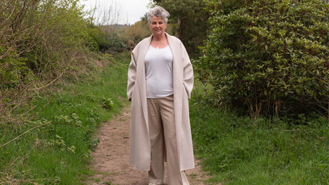 Photo showing Maxine Laceby, a white lady with short curly silver hair, standing outside by some hedges and wearing a long cream coat