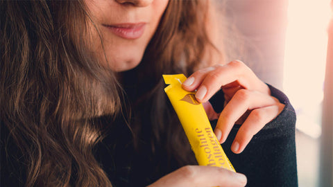Photo of a white woman with long brown hair holding an Absolute Collagen sachet to her mouth