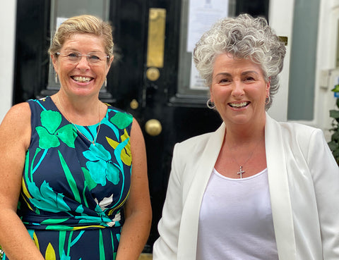 Photo of two white women smiling against a black door, one woman wears green and blue, one woman wears cream and white