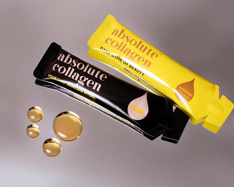 Photo of two sachets of Absolute Collagen, one yellow sachet and one black, lying on a grey surface, with droplets of liquid collagen next to them.