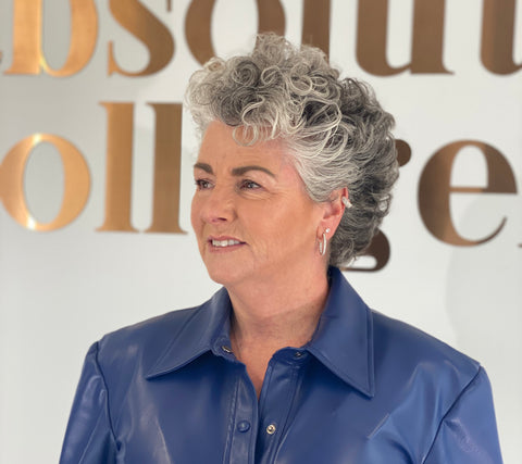 Photo showing a white woman with short wavy silver hair smiling and glancing to the left, she is wearing a blue leather top and standing against the words Absolute Collagen in metallic lettering