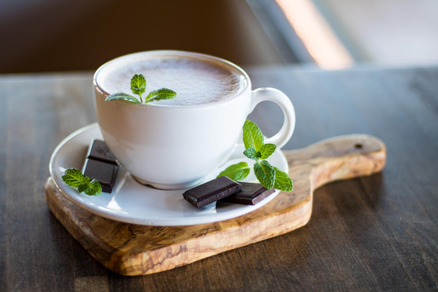 mint tea in a white cup on a wooden board