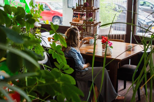 woman drinking tea in cafe looking out of window