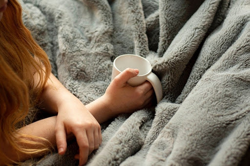 woman holding white cup under grey blanket