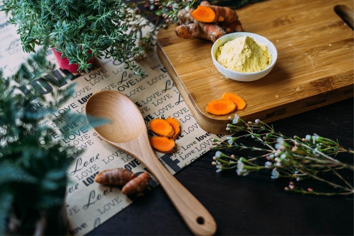 chopped turmeric, powder, herbs and wooden spoon