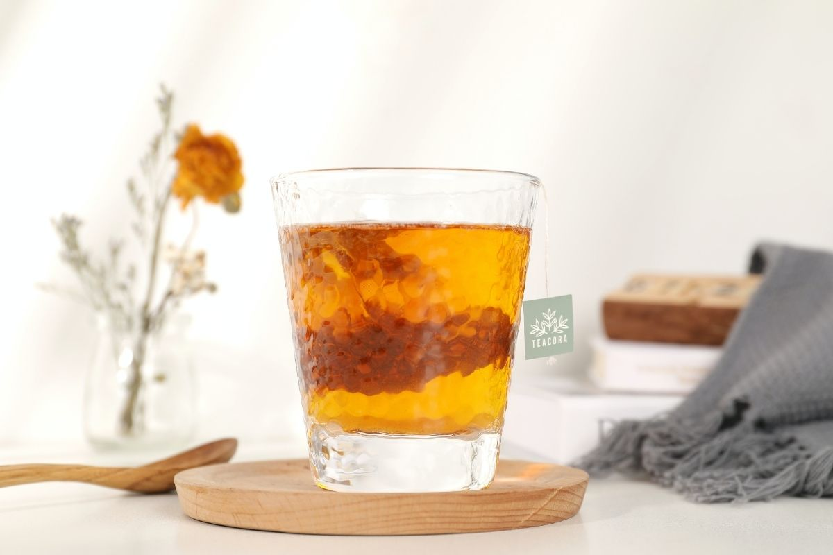 glass of rooibos tea next to yellow flower and scarf