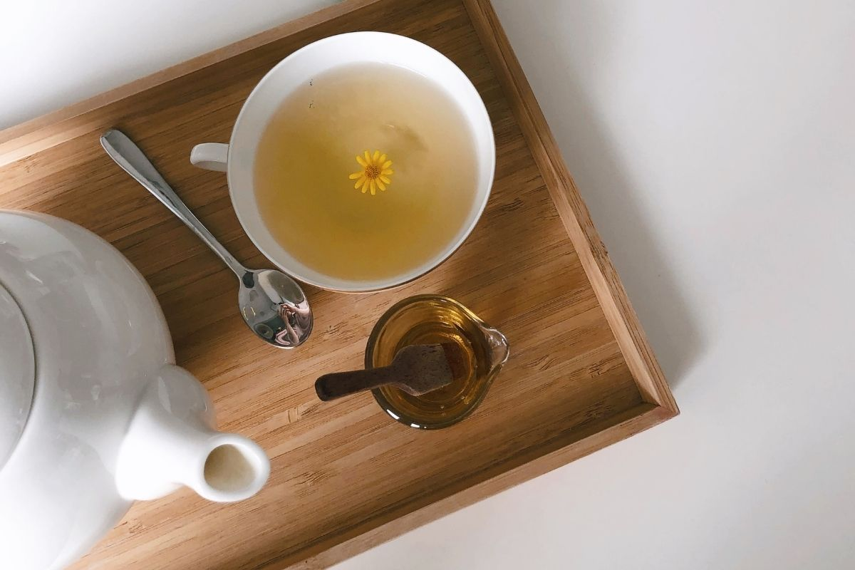 teapot and cup of tea with yellow flower in it
