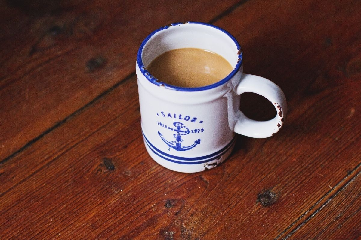 cup of black tea with milk in sailor cup