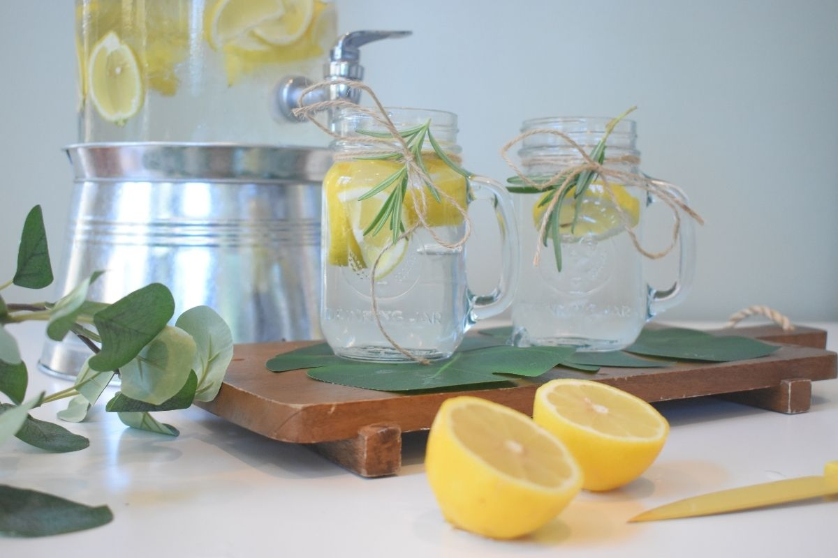 lemons in water with jug and flowers