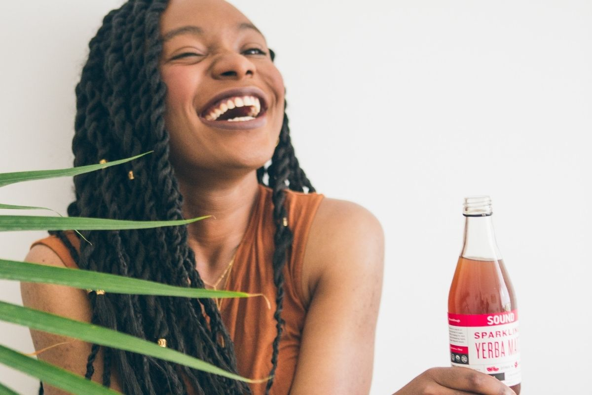 woman laughing and holding a yerba tea bottle