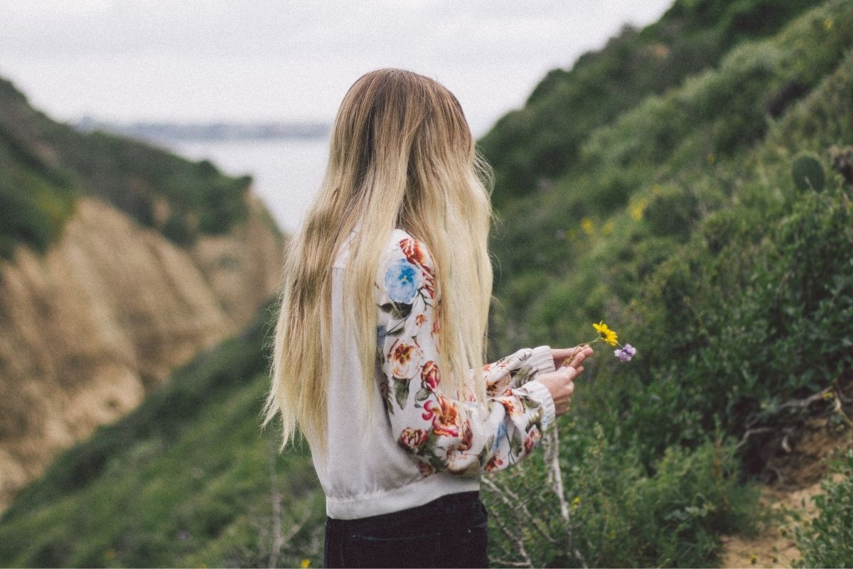 woman with blonde hair picking flowers on a cliff