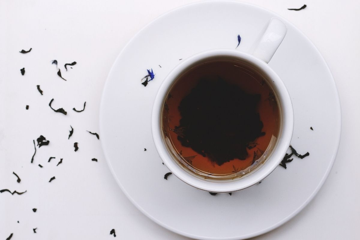 cup of black tea on white saucer