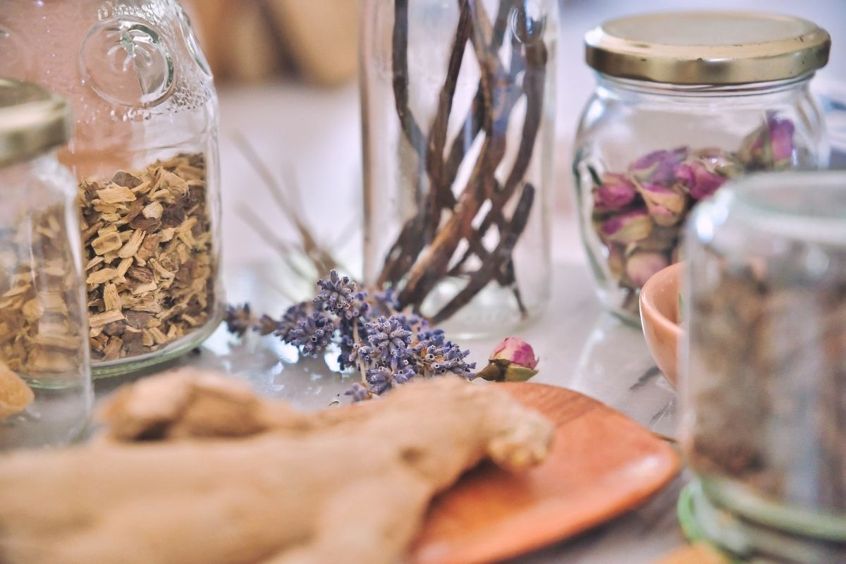 herbs and flowers and ginger root in jars