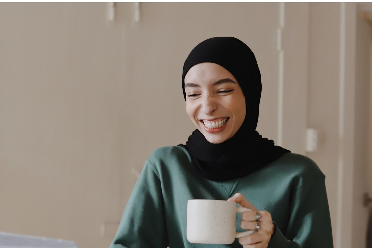 woman with cup of tea laughing