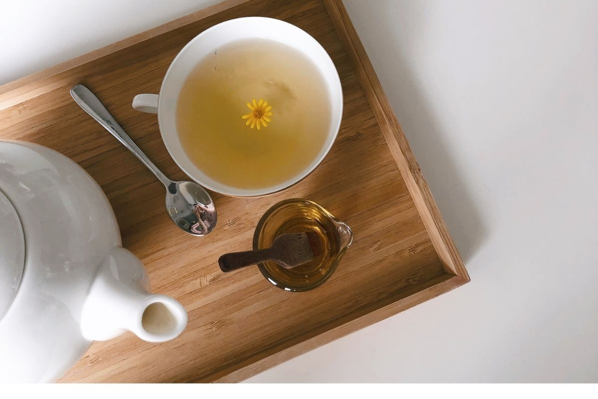 cup of tea with flower in it and teapot with honey
