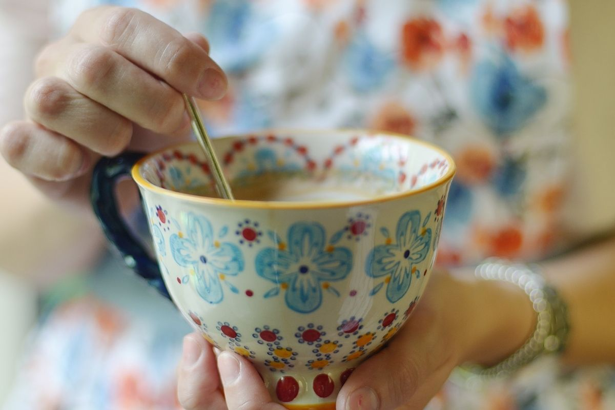 woman stirring tea for acid reflux in flowery cup