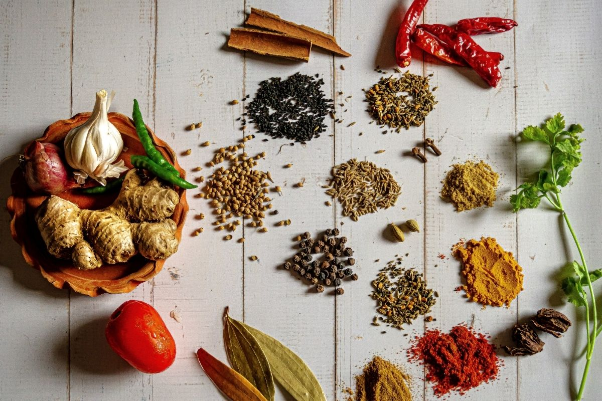 collection of loose spices and herbs on table