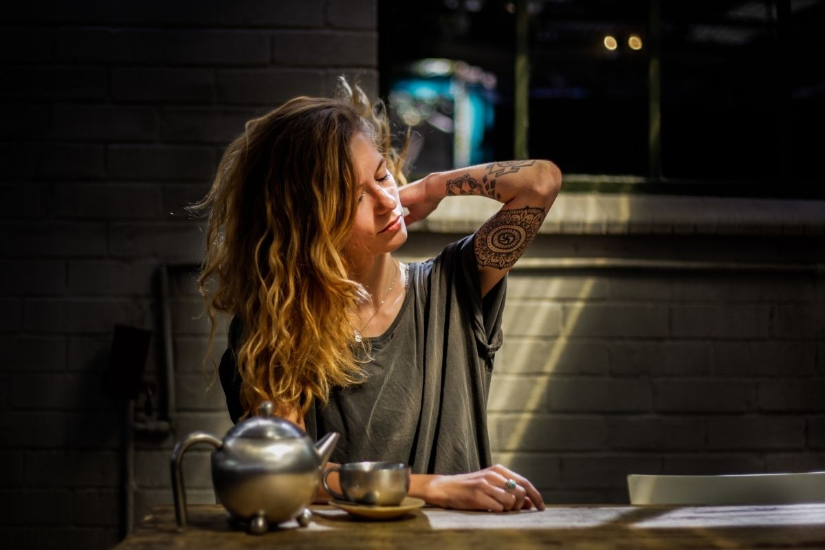 woman sat at table in dark with tea and teapot
