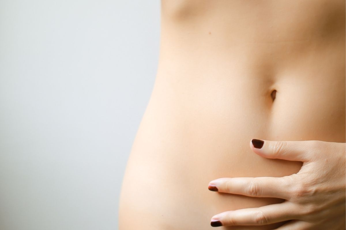 woman with hand on bare stomach