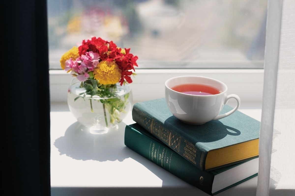 cup of tea on windowsill with books and flowers