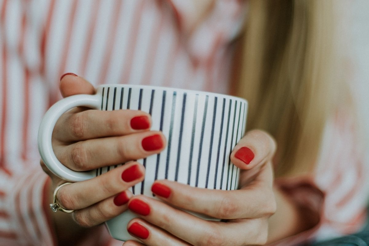 womans hands holding striped cup of tea