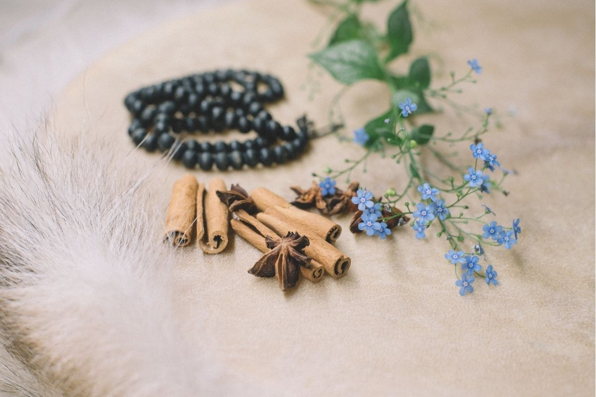cinnamon, flowers, and beads on white rug