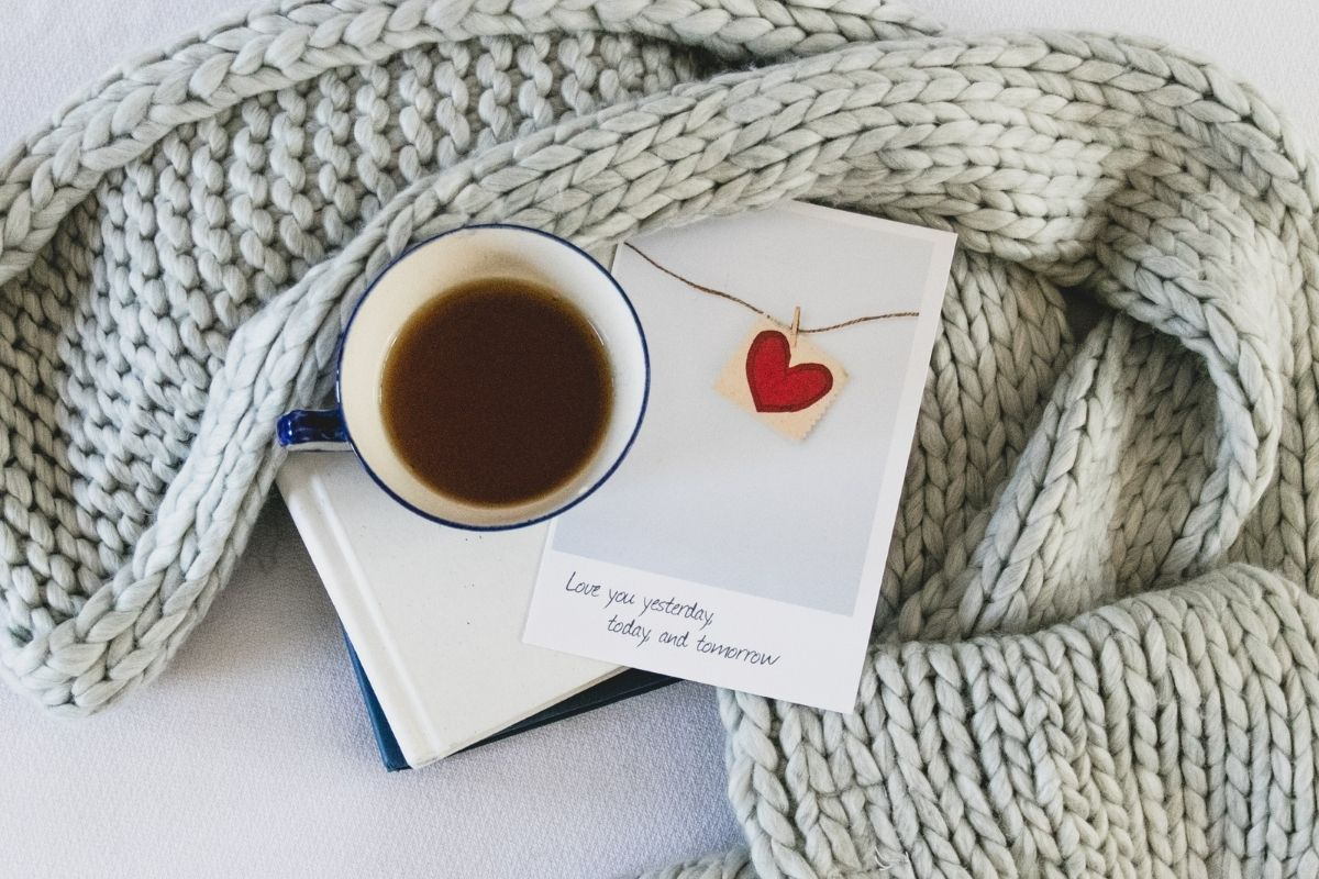 cup of tea next to knitted scarf and heart