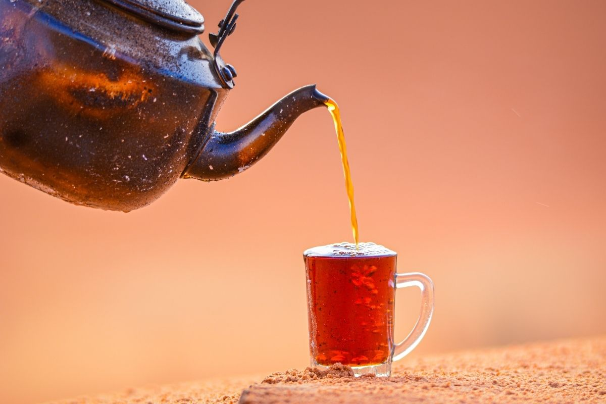 cup of tea being poured from kettle against sandy backdrop