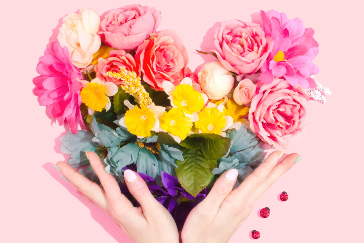 hands holding flowers in shape of a heart