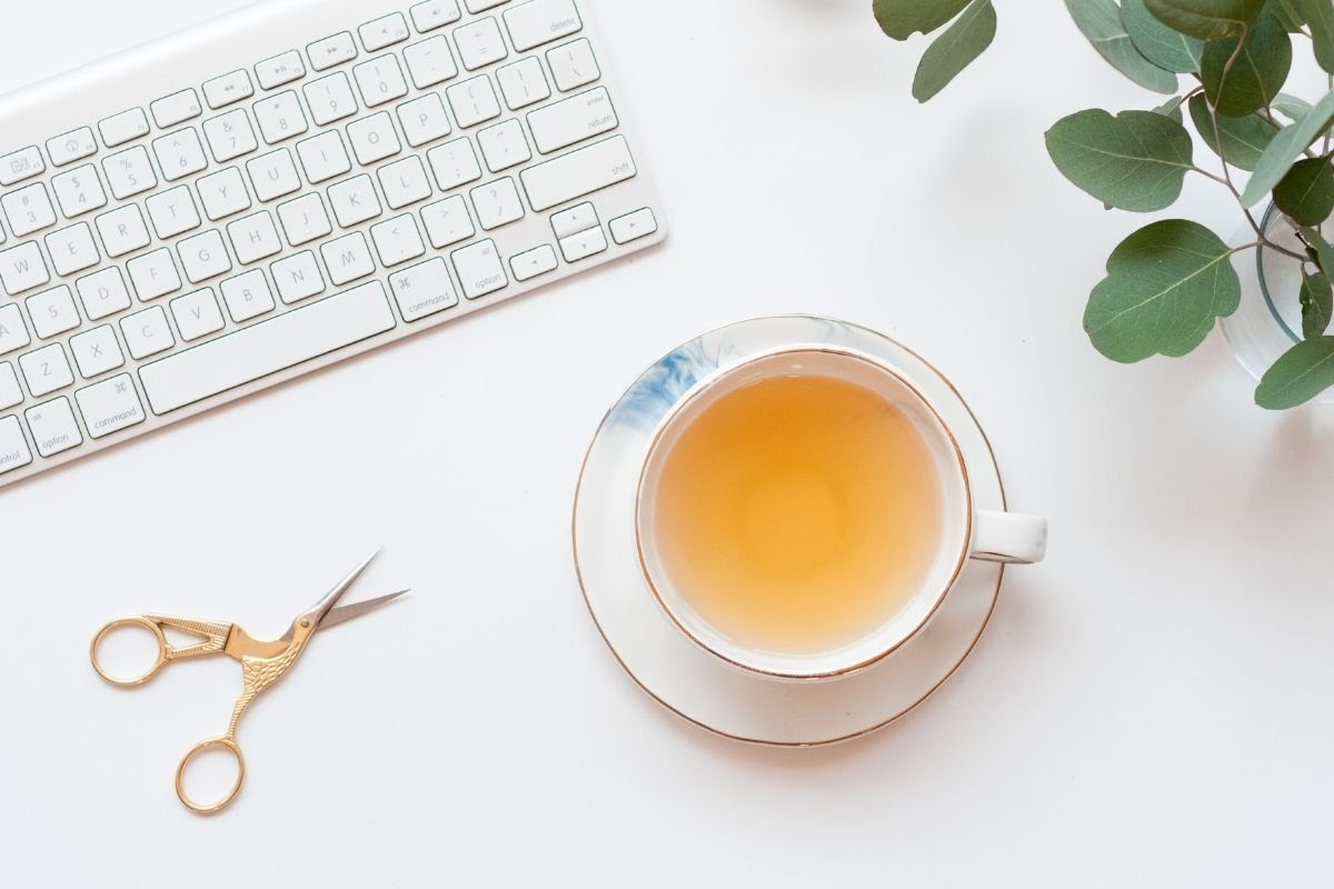 pale cup of tea on white table near keyboard, scissors and plant